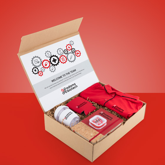 Gift box with shirt, notebook, earbuds, can cozy and tumbler