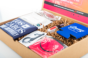 Gift box showing various contents for inspiration such as a mask, can cozy, door opener and a shirt