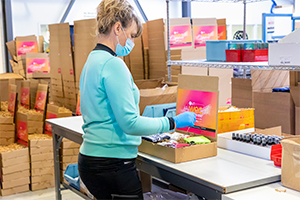 Assembly worker putting together custom gift boxes